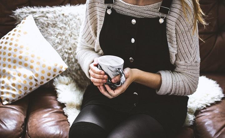 A person holding a mug of tea